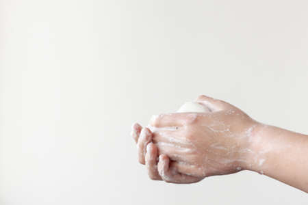 One hand on top, the other on the bottom hold the soap between the soapy palms on a white background. The concept of the need to wash hands to prevent diseases Archivio Fotografico