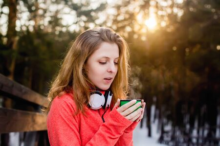 warms: The girl warms her hands on a mug of tea in winter Park Stock Photo