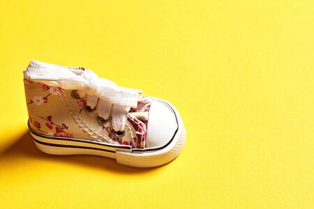 Baby girl sneakers decorated with paints and patterns isolated on the yellow background. Sale and advertisement backdrop