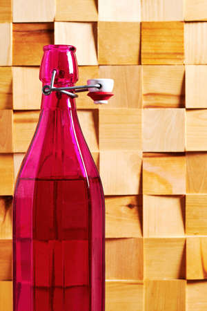 Vintage pink rare wine bottle on the wooden table in the cellar. Wine drinks and rare handmade beverage