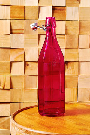 Vintage faceted medieval pink bottle of wine on a traditional winery table. Wooden table and walls in the cellar. Copy space for advertisement text