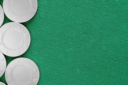 Silver gambling chips on the green poker table surface. Copy space for advertisement text