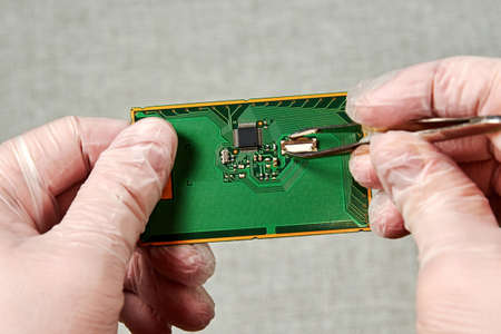 An engineer with tweezers repairing the pcb with a small microchip. Manufacture work processes concept