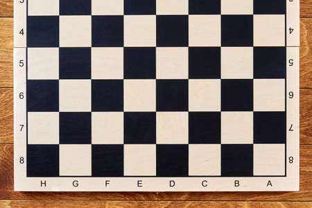Classic empty half chessboard on the brown wooden table. Layout template for chess strategy and tasks. Intellectual games