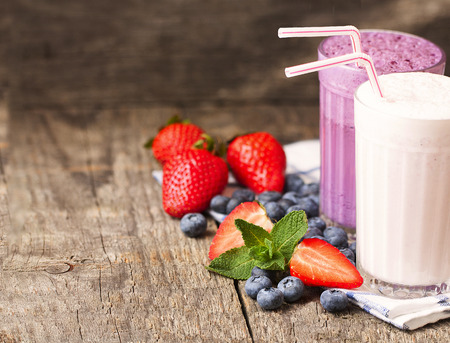 two glasses of milk shakes and fresh berries on a dark wooden background photo