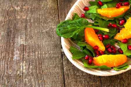 spinach salad: spinach salad, orange and pomegranate on a wooden background