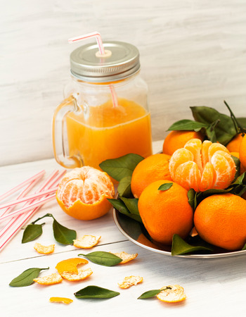 Fresh tangerines with green leaves on a tray on a light wooden background. Glass jar with fresh tangerine juice and a straw.   Natural style. Standard-Bild