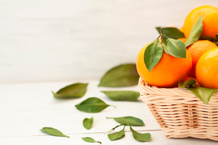Fresh tangerines with green leaves in a wicker basket on a light wooden background. Natural style. Stok Fotoğraf