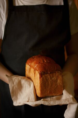 A loaf of freshly baked white bread in the hands of a baker. Baker in a black apron. Bread lies on a linen napkin.