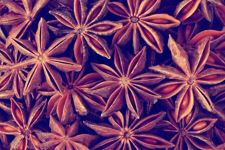 Christmas mood food background: scattered anise stars with seeds. Warming Christmas spices.