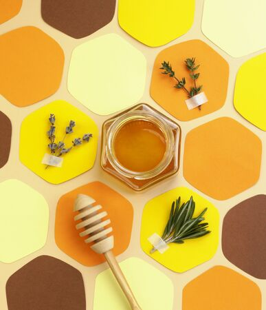 Collage - a jar of honey in the shape of a hexagon and a honeycomb, cut out of colored paper, with melliferous herbs and a spoon for honey. Bright colors, top view. Vertical format, social-media-ready.