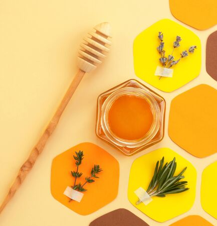 Collage - a jar of honey in the shape of a hexagon and a honeycomb, cut out of colored paper, with melliferous herbs and a spoon for honey. Bright colors, top view, square, social-media-ready. Zdjęcie Seryjne