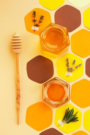 Collage - a jar of honey in the shape of a hexagon and a honeycomb, cut out of colored paper, with melliferous herbs and a spoon for honey. Bright colors, top view, Vertical format, social-media-ready.