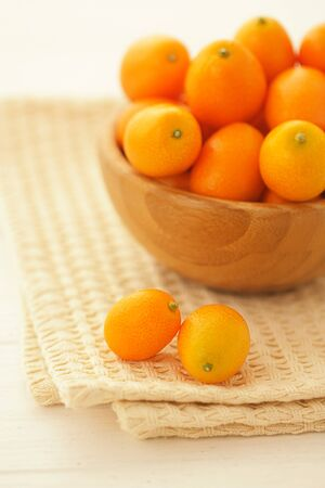 Fresh kumquats in a wooden bowl on a table covered with a light cotton napkin. Vertical format