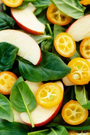 Light and nutritious salad: fresh spinach leaves, slices of fresh apples and slices of juicy kumquats Zdjęcie Seryjne