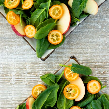 Two plates with a salad of fresh spinach, apples and kumquats on a light wooden background. Square format.