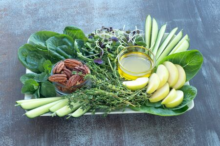 Romano lettuce leaves, fresh cucumber and green Apple, sliced, microgreens, fresh thyme, mint, pecans and olive oil on wooden table