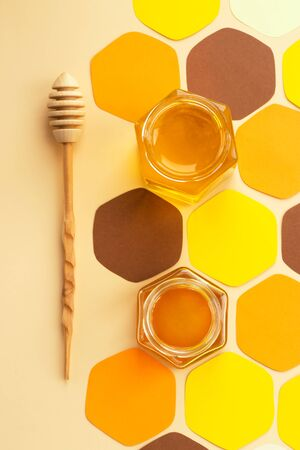 Collage: two jars of honey, a wooden spoon for honey and a stack of paper.