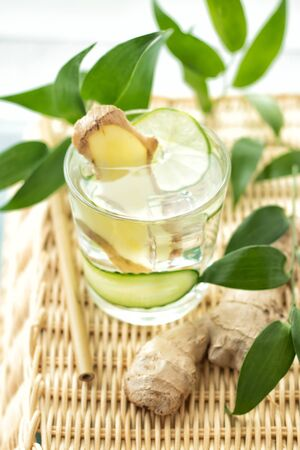 glass of ginger water with cucumber and lime close up