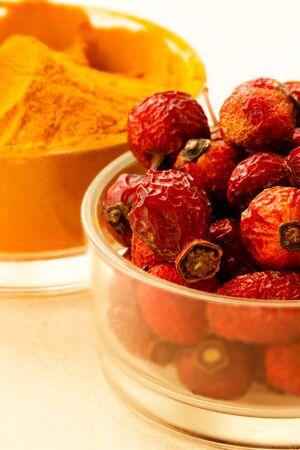 Spices close - up-turmeric powder and rosehip berries. Bright taste and virus protection Zdjęcie Seryjne
