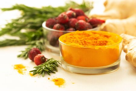 Turmeric, rosehip berries, ginger and rosemary on a light background. Bright taste, health improve and protection from viruses.