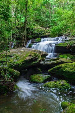 Tham yai waterfall, a beautiful waterfall in a forest filled with green trees at Phu Kradung National Park in the rainy season, which is famous tourist destination in Thailand.