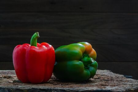 Red and green peppers (Sweet peeper or bell pepper or Capcicum.) Green peppers on wooden with brown background.