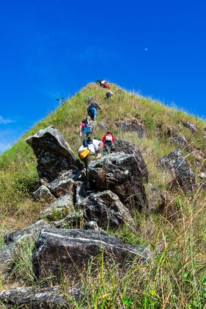 Group of tourists climbing up the mountain top with a blue sky background in Thongphaphum National Park, ,Khao Chang Phueak, Thailand.