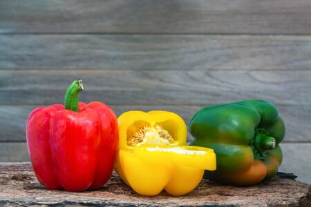 Red, yellow and green peppers (Sweet peeper or bell pepper or Capcicum.)  on wooden with brown background. Standard-Bild