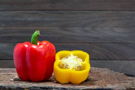 Red and yellow peppers (Sweet peeper or bell pepper or Capcicum.)  on wooden with brown background. Standard-Bild