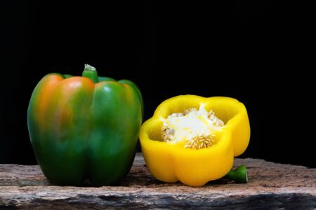 Bell pepper (Sweet pepper or Capcicum.)  , yellow and green peppers on wooden with black background.