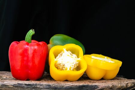 Bell pepper (Sweet pepper or Capcicum.)  Red, yellow and green peppers on wooden with dark background.