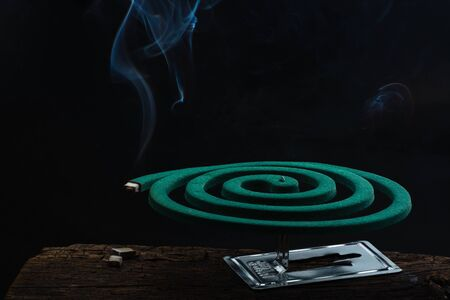 Burning green spiral mosquito repellent coil and with white smoke on dark background.