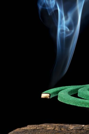 Burning green spiral mosquito repellent coil and red fire  with white smoke on black background.