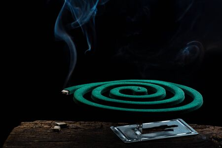 Burning green spiral mosquito repellent coil and with white smoke on black background. Standard-Bild