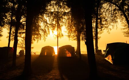 The image of  camping tents and activity on the beach in the morning with golden sky and sunrise. Hat Wannakon, a beach filled with pine trees in Thailand. Standard-Bild