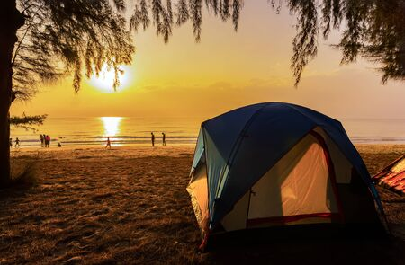 The image of a camping tent and activity on the beach in the morning with golden sky and sunrise. Hat Wannakon, a beach filled with pine trees in Thailand.