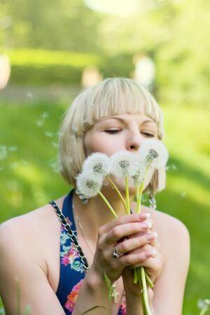 A young girl blowing on dandelions in a sunny day