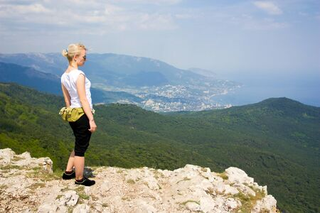 Woman tourist is standing at the top of a mountain Stock Photo