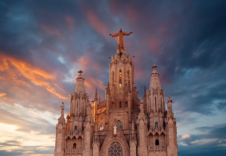 cor: The Sagrat Cor church atop the mountain. Church atop the mountain against the background a beautiful sunset sky. Barcelona, Spain.