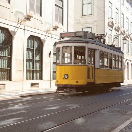 trams: Traditional yellow trams on a street in Lisbon, Portugal