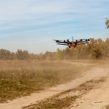 raises: Copter flying at speed. Copter flying above the road and raises for a dust