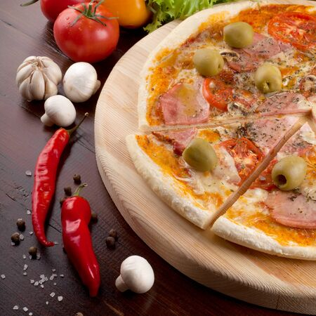 Rustic pizza with ham, mozzarella, olive and mushroom. Pizza is on a beautiful wooden table. Top view. Stock Photo