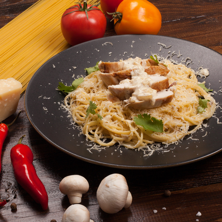 Spaghetti in a white sauce with chicken breast. The composition with ingredients on a dark wooden background.