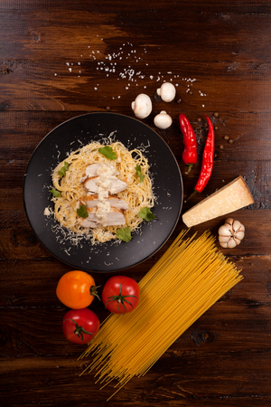 Spaghetti in a white sauce with chicken breast. The composition with ingredients on a dark wooden background. Top view. Stock Photo
