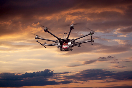spy camera: Flying copter with their gear on the background of a beautiful sunset. Stock Photo