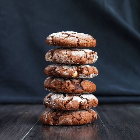 Chocolate cookies, sprinkle with powdered sugar. Folded on each other. Cookies on a dark background
