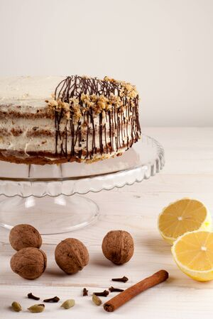 carrot cake: Carrot cake with walnuts and white cream drizzled with chocolate on a light wooden background. Stock Photo