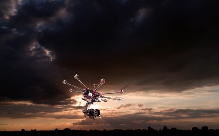 surveillance: Flying copter with their gear on the background of a beautiful sunset. Stock Photo