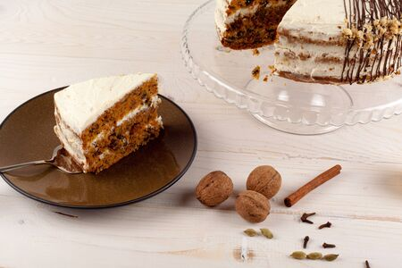 walnut cake: Carrot cake with walnuts and white cream drizzled with chocolate on a light wooden background. Stock Photo